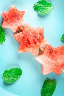 Pastèque en forme d'étoiles sur des brochettes avec des feuilles de menthe se trouve sur une plaque bleue. vue de dessus.