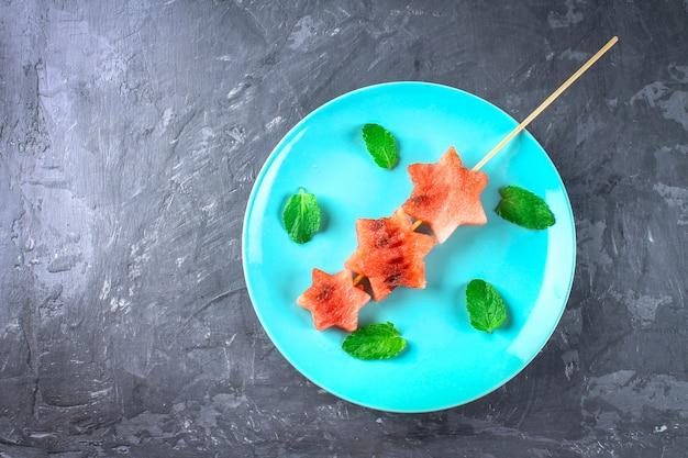 Pastèque en forme d'étoiles sur des brochettes avec des feuilles de menthe se trouve sur une plaque bleue.