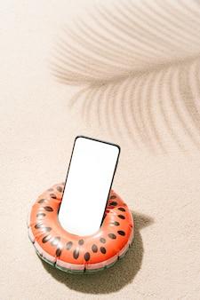 Pastèque gonflable en forme de téléphone portable à l'intérieur sur le sable d'une plage tropicale avec des ombres de feuilles de cocotier en été