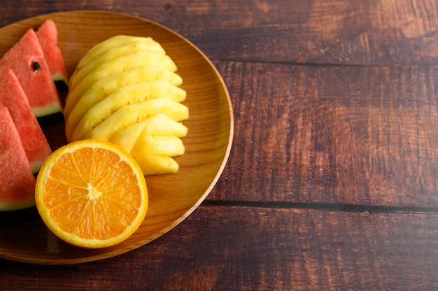 Pastèque, orange et ananas coupés en morceaux sur une plaque en bois