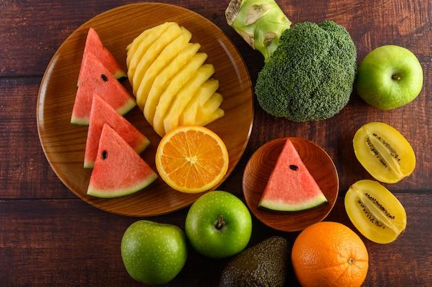 Pastèque, orange, ananas, kiwi coupés en tranches avec des pommes et du brocoli sur une plaque en bois et une table en bois.