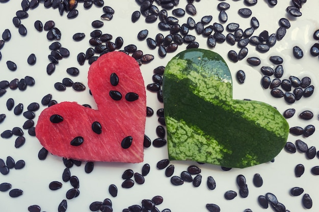 Pastèque, sculptée en forme de coeur. sur la table lumineuse, il y a beaucoup de graines de melon d'eau. concept - été, amour, végétarisme, nourriture crue.