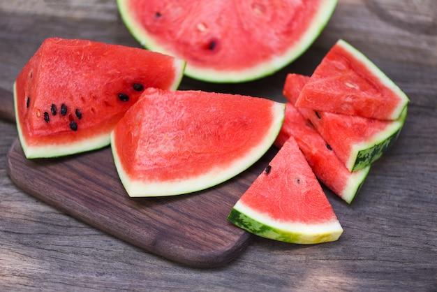 Pastèque en tranches sur fond de planche à découper en bois - gros plan morceaux de pastèque fraîche fruits d'été tropicaux