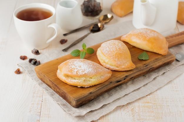 Pasties avec du fromage cottage et du sucre en poudre sur un fond en bois clair pâtisserie traditionnelle russe sochnik