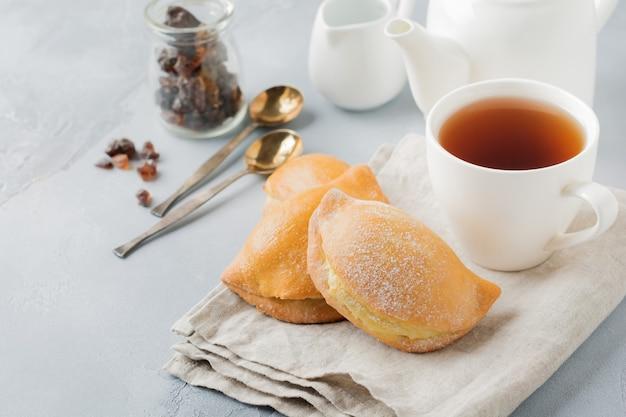 Pasties avec du fromage cottage et du sucre en poudre sur une pierre grise ou un fond de béton pâtisserie traditionnelle russe sochnik