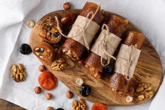 Pastille de fruits aux fruits secs, noix et miel enveloppé dans du papier sulfurisé sur planche de bois sur blanc