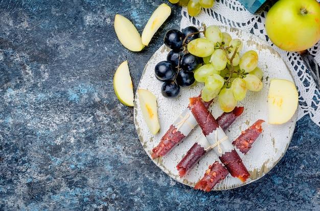 Pastille de pommes fraîchement cueillies et raisins et fruits sur fond sombre