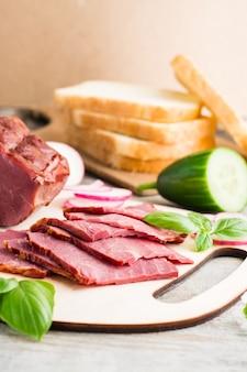 Pastrami de boeuf marbré tranché frais, concombre, radis et basilic sur une planche à découper. délicatesse américaine. style rustique.