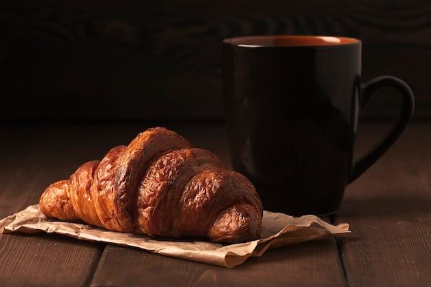 Pastriescroissants sur une table en bois marron avec une tasse de café petit-déjeuner sans style rustique de personnes