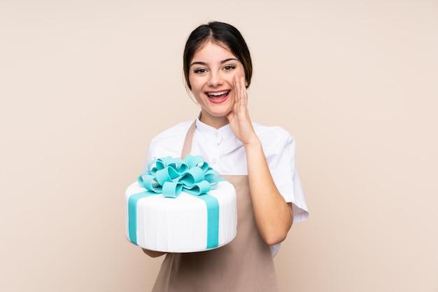 Pastry chef woman holding a big cake crier avec la bouche grande ouverte