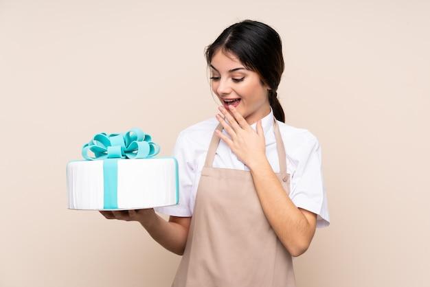 Pastry chef woman holding a big cake avec surprise et expression faciale choquée