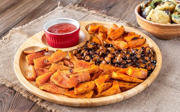 Patate douce au four avec champignons frits sur le plateau en bois