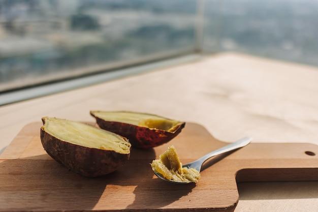 Patate douce coupée en deux avec une cuillère à café sur planche de bois