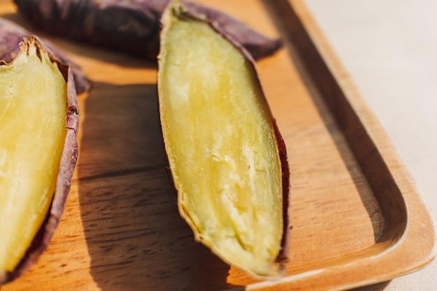 Patate douce coupée en deux sur plaque de bois