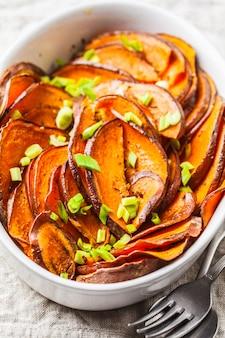 Patate douce tranchée au four avec oignons verts dans un plat blanc.