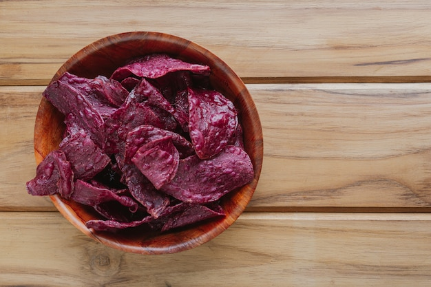 Patate douce violette dans la tasse, posée sur un plancher de bois brun.