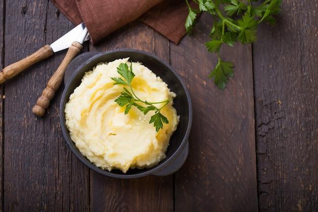 Patate. purée de pommes de terre ou purée bouillie de persil en pot en fonte sur table rustique en bois foncé. vue de dessus