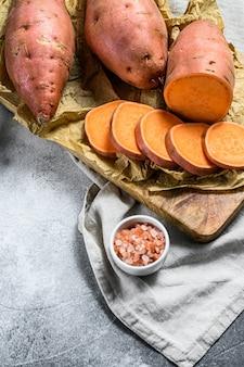 Patates douces crues sur une planche à découper, igname bio.