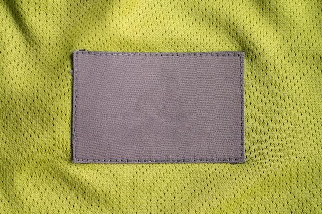 Patch d'étiquette de vêtements de soin de blanchisserie sur la texture de sport de jersey de tissu de polyester