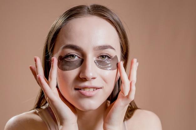 Patch pour les yeux, belle femme avec maquillage naturel et patchs pour les yeux hydro gel noir sur la peau du visage.
