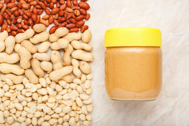Pâte d'arachide crémeuse dans un bocal en verre avec un bouchon jaune et des arachides dans la coque et des arachides décortiquées.