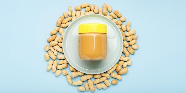 Pâte d'arachide crémeuse dans un bocal en verre avec bouchon jaune et cacahuètes en pelure éparpillées sur fond bleu