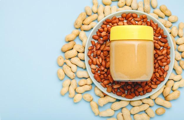 Pâte d'arachide crémeuse dans un bocal en verre avec capuchon jaune et arachides sur fond bleu pour la cuisson du petit-déjeuner. concept de cuisine végétalienne. plat de nourriture minimaliste avec espace de copie sur fond de couleur.