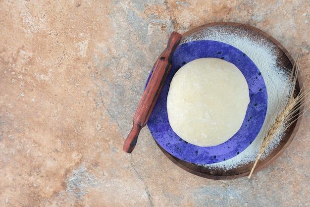 Pâte au rouleau à pâtisserie et farine sur marbre