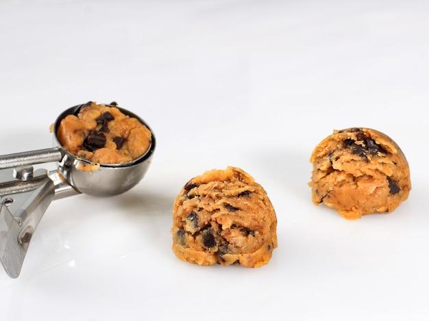 Pâte à biscuits crue isolée sur fond blanc avec une cuillère à crème glacée pour mesurer sur l'arrière-plan. home baker, étape par étape, faire des biscuits aux pépites de chocolat.