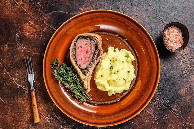 Pâte de boeuf wellington avec pommes de terre en purée sur une assiette rustique.