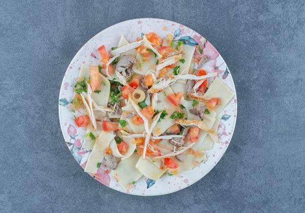 Pâte bouillie avec des légumes hachés sur une assiette colorée.