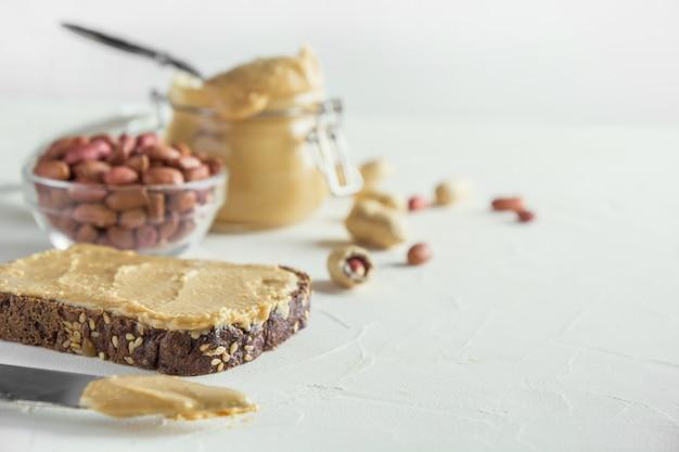 Pâte de cacahuètes sur pain brun complet. alimentation saine.