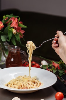 Pâte de carbonara appétissante avec du poulet mal enroulé sur une fourchette.