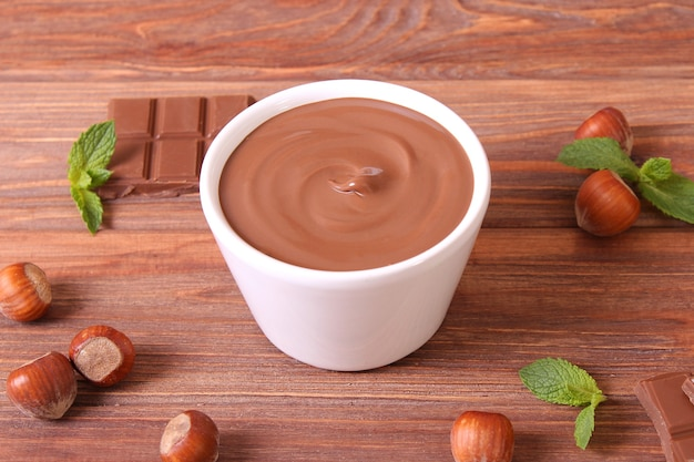 Pâte de chocolat dans un bocal en verre sur fond coloré