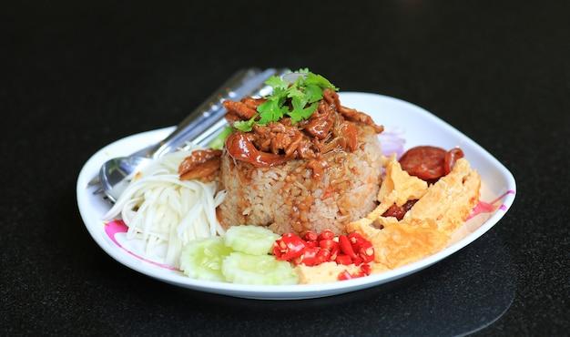 Pâte de crevettes au riz frit avec du porc et œuf au plat dans une assiette sur un tableau noir.