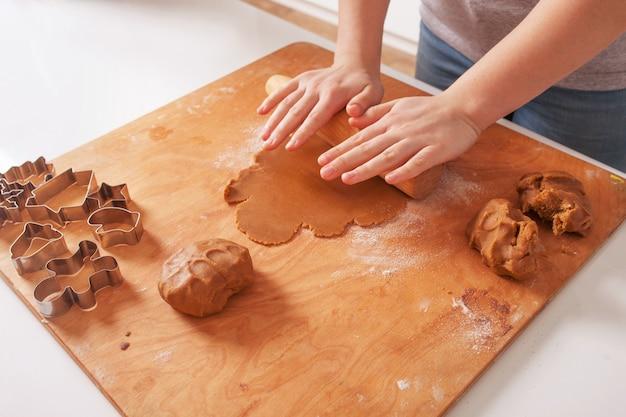 Pâte crue, emporte-pièce et rouleaux à pâtisserie pour biscuits de noël