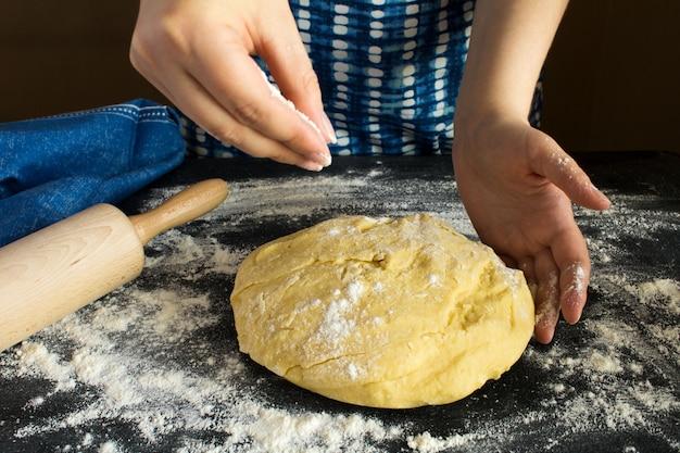 Pâte crue pour la cuisson et les mains des femmes sur le fond sombre