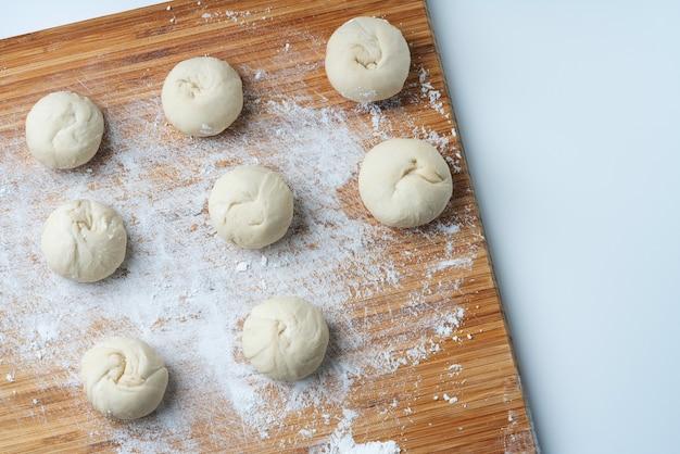 Pâte crue pour faire des petits pains asiatiques. sur une planche à découper en bambou. processus de cuisson fait maison. vue de dessus. mise à plat.