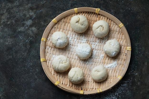 Pâte crue pour faire des petits pains asiatiques sur un plateau en bambou traditionnel. processus de cuisson fait maison. vue de dessus. mise à plat.