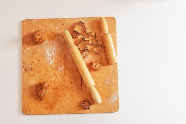 Pâte crue et rouleaux à pâtisserie pour biscuits de noël. emporte-pièces - arbre de noël, flocon de neige, clochette, bonhomme en pain d'épice. pâtisserie de noël. préparation pour les vacances, noël, nouvel an. espace de copie