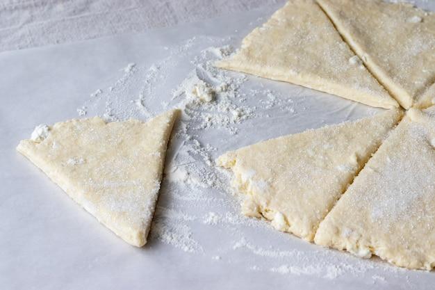 Pâte crue roulée coupée en huit triangles saupoudrée de sucre sur du papier sulfurisé