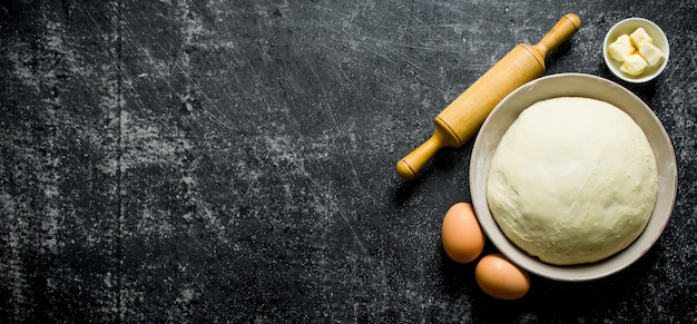 Pâte dans un bol avec des œufs, rouleau à pâtisserie et beurre sur table rustique