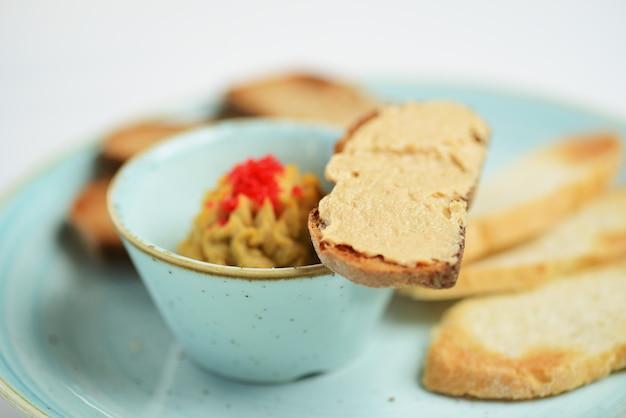 Pate dans un bol avec des tranches de pain grillé