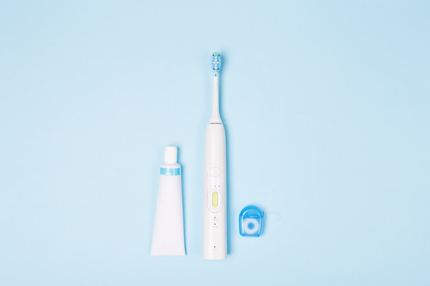 Pâte à dents en tube, soie et brosse à dents sur fond bleu clair. copiez l'espace.