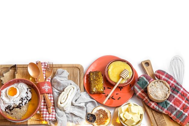 Pâte, différents couteaux et ingrédients pour les biscuits de noël sur une table en bois blanche, à plat.