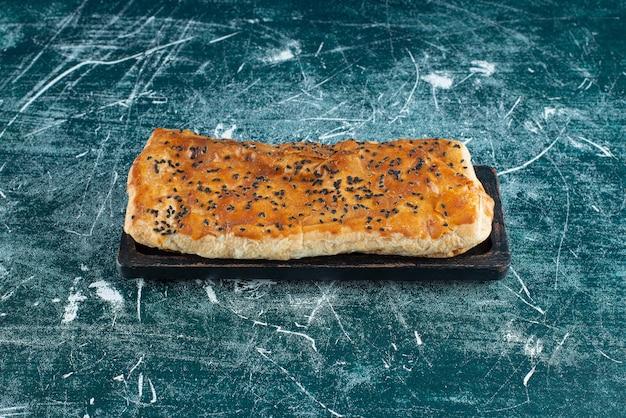 Pâte farcie aux graines de sésame sur une surface en marbre.