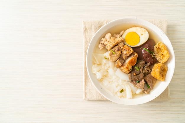 Pâte de farine de riz ou carré de pâtes chinoises bouillies avec du porc dans une soupe claire - style de cuisine asiatique