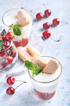 Pâte feuilletée aux cerises d'été avec biscuits savoiardi et fromage à la crème en verre sur fond gris clair. gâteau tiramisu traditionnel avec des baies fraîches. mise au point sélective.