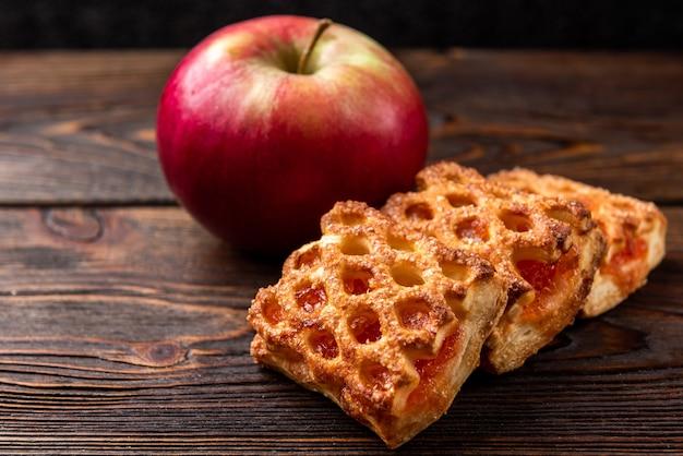 Pâte feuilletée aux pommes sur table en bois sombre.