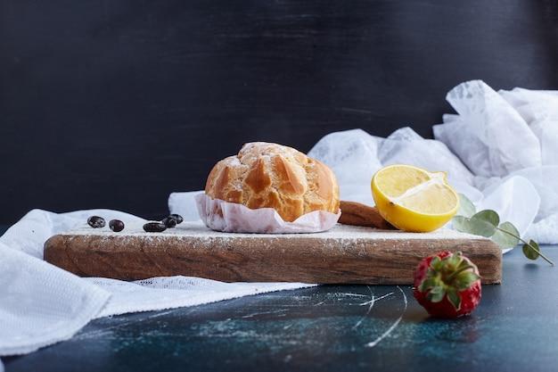 Pâte feuilletée avec un citron sur planche de bois.